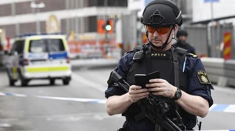 Un policier vérifie son téléphone après l'attaque de Stockholm