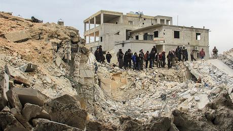 Des personnes creusent à travers les débris d'une mosquée dans le village d'al-Jineh après la frappe aérienne américaine