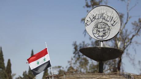 Un drapeau de la République arabe syrienne à côté d'un emblème de l'Etat islamique