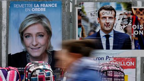Une affiche de Marine Le Pen et une affiche dégradée d'Emmanuel Macron dans les rues de Béthune