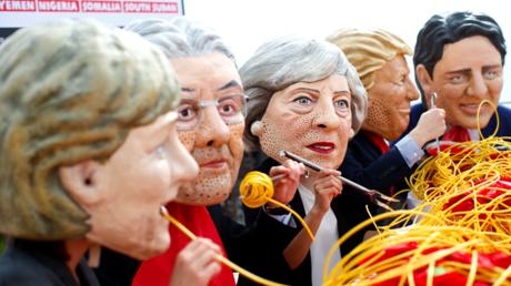 Des militants d'Oxfam arborant des masques à l'effigie des dirigeants des grandes puissances mondiales, en train d'avaler goulûment des plats de spaghettis. Taormine, Sicile, le 26 mai 2017.
