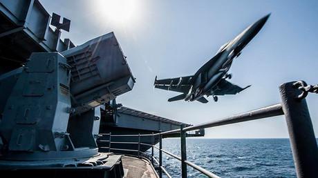 Un avion de combat américain F/A-18 Hornet décolle depuis le porte-avions Carl Vinson.