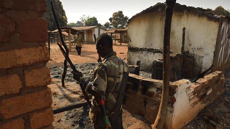 Un combattant anti-Balaka inspecte les ruines des bâtiments incendiés par des combattants de la Séléka en janvier 2014 , photo ©ERIC FEFERBERG / AFP