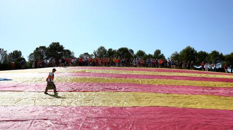 Un homme marche sur un drapeau géant de la Catalogne