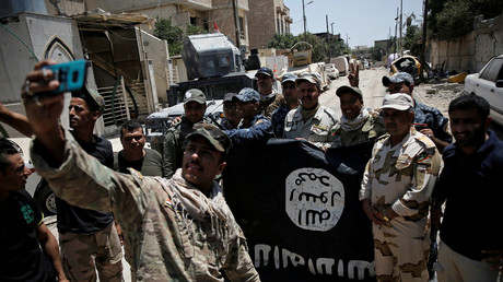 Soldats irakiens posant avec un drapeau de l'EI capturé à Mossoul en juillet 2017
