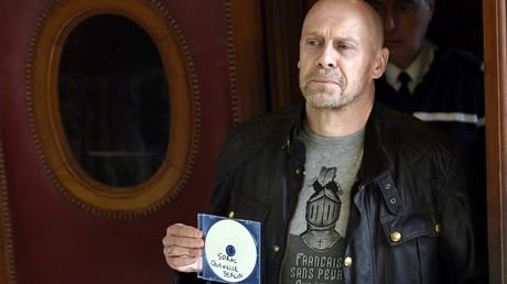 Alain Soral brandissant un CD devant la chambre où se tenait un de ses procès en 2015 à Paris