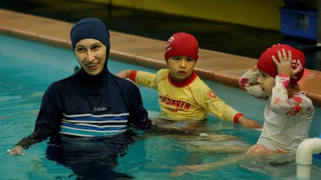 Une femme en burkini entourée d'enfants dans une piscine (image d'illustration)