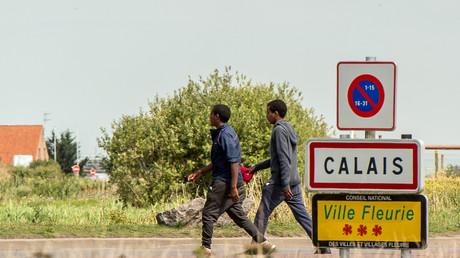 Des migrants marchent à l'entrée de Calais le 1 août 2017.