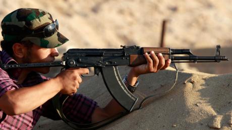 Un combattant rebelle libyen s'entraîne à tirer à la kalachnikov près de Misrata, en juin 2011
