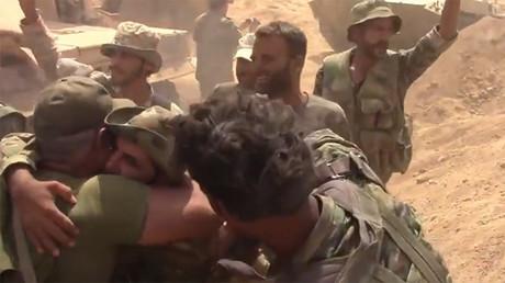 Des soldats de l'armée gouvernementale syrienne embrassent leurs compagnons d'armes après avoir libéré leur base, encerclée par l'Etat islamique depuis 2014