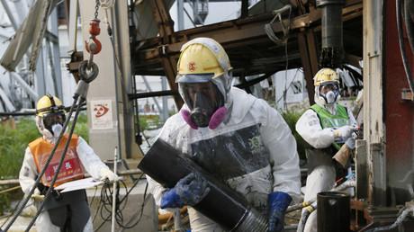 Ouvriers œuvrant pour la décontamination du site de Fukushima, en pleine construction d'un mur de glace autour de quatre unités du site.