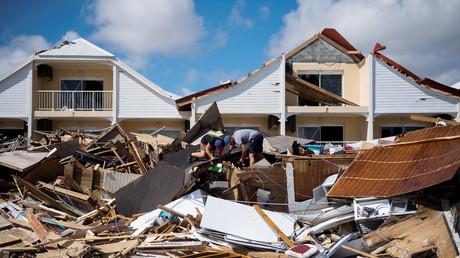 Deux hommes recherchent des affaires dans les débris de leur restaurant sur la plage d'Orient Bay à Saint-Martin, dévastée par l'ouragan Irma, le 10 septembre 2017
