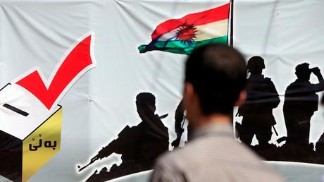 Un homme se tient devant une affiche en faveur du referendum pour le Kurdistan en Irak à Erbil, le 24 septembre