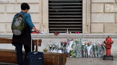 Une personne se recueille devant le mémorial improvisé dédié aux deux victimes de l'attentat de Marseille, face à la gare Saint-Charles.