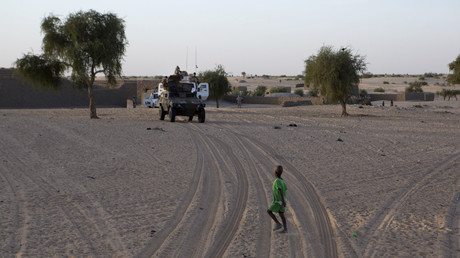 Un enfant traverse devant un convoi militaire de l'opération Barkhane, près de Tombouctou