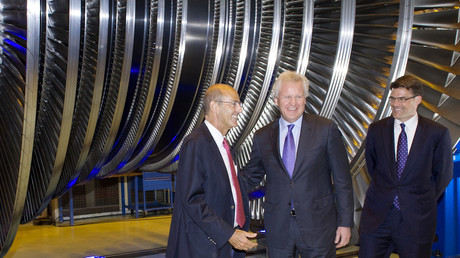 Patrick Kron, PDG d'Alstom (droite) et Jeffrey R. Immelt (centre), PDG de General Electric en 2014,  posent devant une turbine Alstom, photo ©SEBASTIEN BOZON / AFP