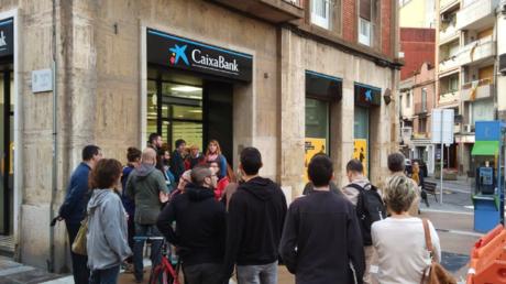 Des catalans retirant leur argent à l'appel d'associations indépendantistes