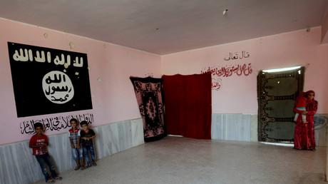 Enfants posant près d'un mur peint aux couleurs de Daesh près de Deir ez-Zor en Syrie en octobre 2017.