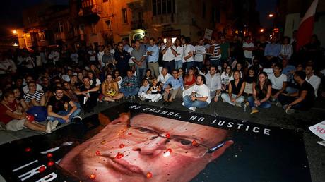 Les manifestants ont déployé un portrait géant du chef de la police, Lawrence Cutajar, qu'ils ont recouvert de tomates et de pièces de monnaie.
