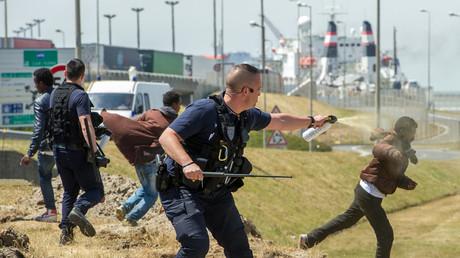 Policier utilisant du gaz lacrymogène sur un migrant à Calais en 2015