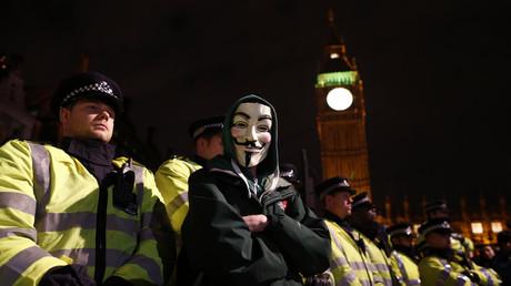 Un manifestant arborant un masque de Guy Fawkes prend la pose devant les forces de l'ordre à Londres en novembre 2013
