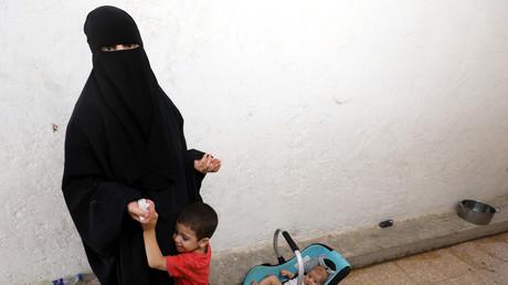 une femme dont les membres de la famille ont été accusés de faire partie de l'Etat islamique, photographiée avec ses enfants, le 22 juillet 2017 dans un camp de déplacés près du village d'Ain Issa.