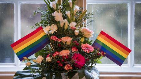 Bouquet de mariage flanqué d'un drapeau gay