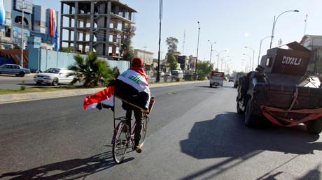 Un homme à bicyclette dans les rues de Kirkouk après l'annonce de la libération totale du territoire irakien