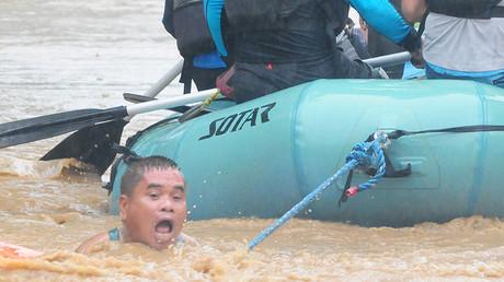 Un homme s'accroche à une corde attachée à un canot de sauvetage, alors que les habitants de la ville de Cagayan de Oro, aux Philippines, sont évacués, le 22 décembre.
