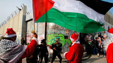Des Palestiniens pacifiques déguisés en pères Noël affrontent les soldats israéliens à Bethléem