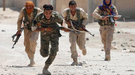 Des combattants kurdes des Unités de protection du peuple (YPG) traversent une rue à Raqqa, en Syrie, le 3 juillet 2017.