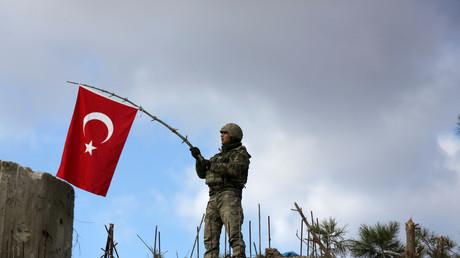 Un soldat turc agitant un drapeau près d'Afrin