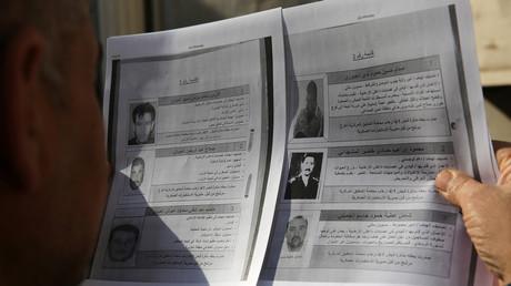 Un homme regarde la liste des 60 terroristes recherchés