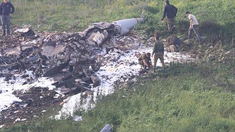Les forces de sécurité israéliennes marchent près des restes du F-16 israélien abattu, près du village israélien de Harduf, le 10 février