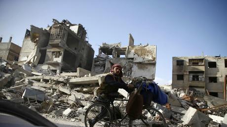 Un homme handicapé, en bicyclette, passe devant des bâtiments endommagés dans la ville assiégée de Douma, dans l'est de la Ghouta.