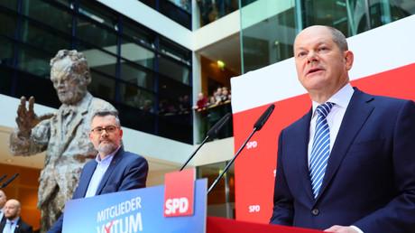 Olaf Scholz (à droite), chef par intérim du parti social-démocrate (SPD) allemand, s'exprime après que le trésorier du SPD, Dietmar Nietan, a annoncé le résultat du référendum du parti SPD
