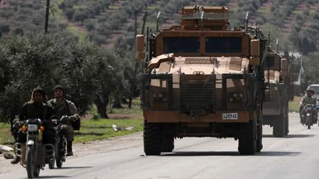 Des combattants de l'Armée syrienne libre (ASL), pro-Ankara, roulant au côté d'un véhicule militaire turc à Afrin, Syrie, le 19 mars 2018