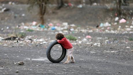 Un garçon se s'appuie sur un pneu dans un camp de fortune au Yémen (Illustration)