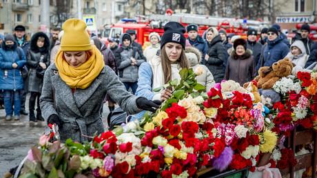 Des passants rendent hommage aux victimes de l'incendie du centre commercial de Kemerovo, photo ©STR / AFP