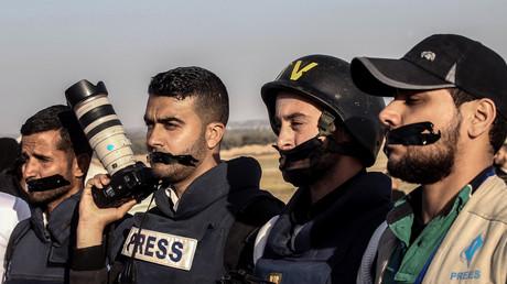 Le 8 avril 2018, des journalistes palestiniens se scotchent la bouche à Rafah, au sud de la bande de Gaza, lors d'une manifestation en l'honneur de leur confrère Yaser Murtafa, tué par les forces israéliennes le 6 avril.