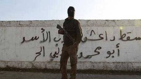 Un combattant de l'armée syrienne libre porte son arme devant un graffiti sur lequel on lit le mot Daesh, dans le quartier de Masaken Hanano à Alep le 7 janvier 2014.