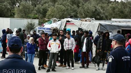 Policiers montant la garde près de migrants au camp de Moria sur l'île de Lesbos, un an après l'accord entre l'Union européenne et la Turquie. A la suite de la fermeture des frontières, 15 000 migrants sont confinés dans les îles grecques.