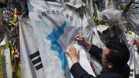 Un homme écrit sur un drapeau de l'unification accroché à la clôture séparant les deux Corées, à Paju, le 26 avril