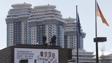 A Moscou, sur le toit de l'ambassade d'Allemagne,  des employés fixent une bannière sur laquelle est écrit, en russe : «L'Allemagne attend avec impatience le championnat du monde de football 2018» (illustration).