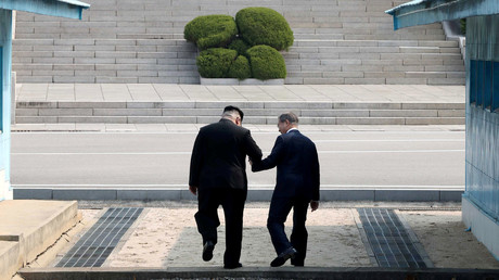 Le dirigeant nord-coréen Kim Jong Un et le président sud coréen Moon Jae In franchissent main dans la main la ligne de démarcation entre les deux Corées, le 27 avril