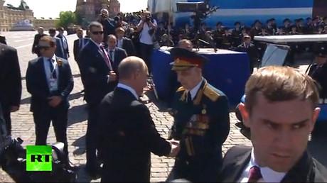 Le président russe Vladimir Poutine sert la main d'un vétéran de la Seconde guerre mondiale le 9 mai 2018 à Moscou.
