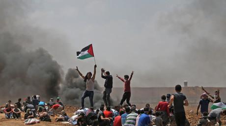 Des Palestiniens brandissent leur drapeau alors qu'ils manifestent près de la frontière entre Israël et la bande de Gaza, contre l'inauguration de l'ambassade des Etats-Unis après son transfert controversé à Jérusalem, le 14 mai 2018