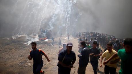 Des manifestants palestiniens sous les tirs de gaz lacrymogènes à la frontière entre Gaza et Israël, le 14 mai 2018