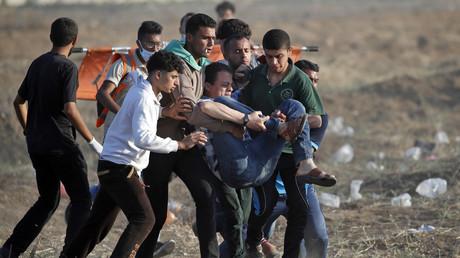 Des Palestiniens portent un manifestant blessé par balle lors d'affrontements avec les forces israéliennes à l'est de Gaza, le 15 mai 2018