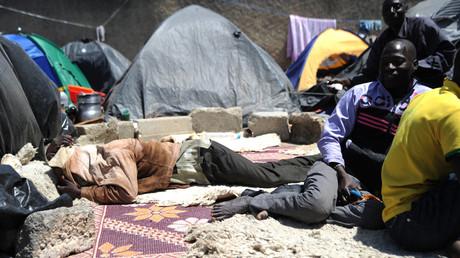 Des migrants clandestins nigériens sont assis près de leurs tentes après s'être installés près du marché aux fruits de la ville algérienne de Boufarik, à 35 km au sud de la capitale Alger